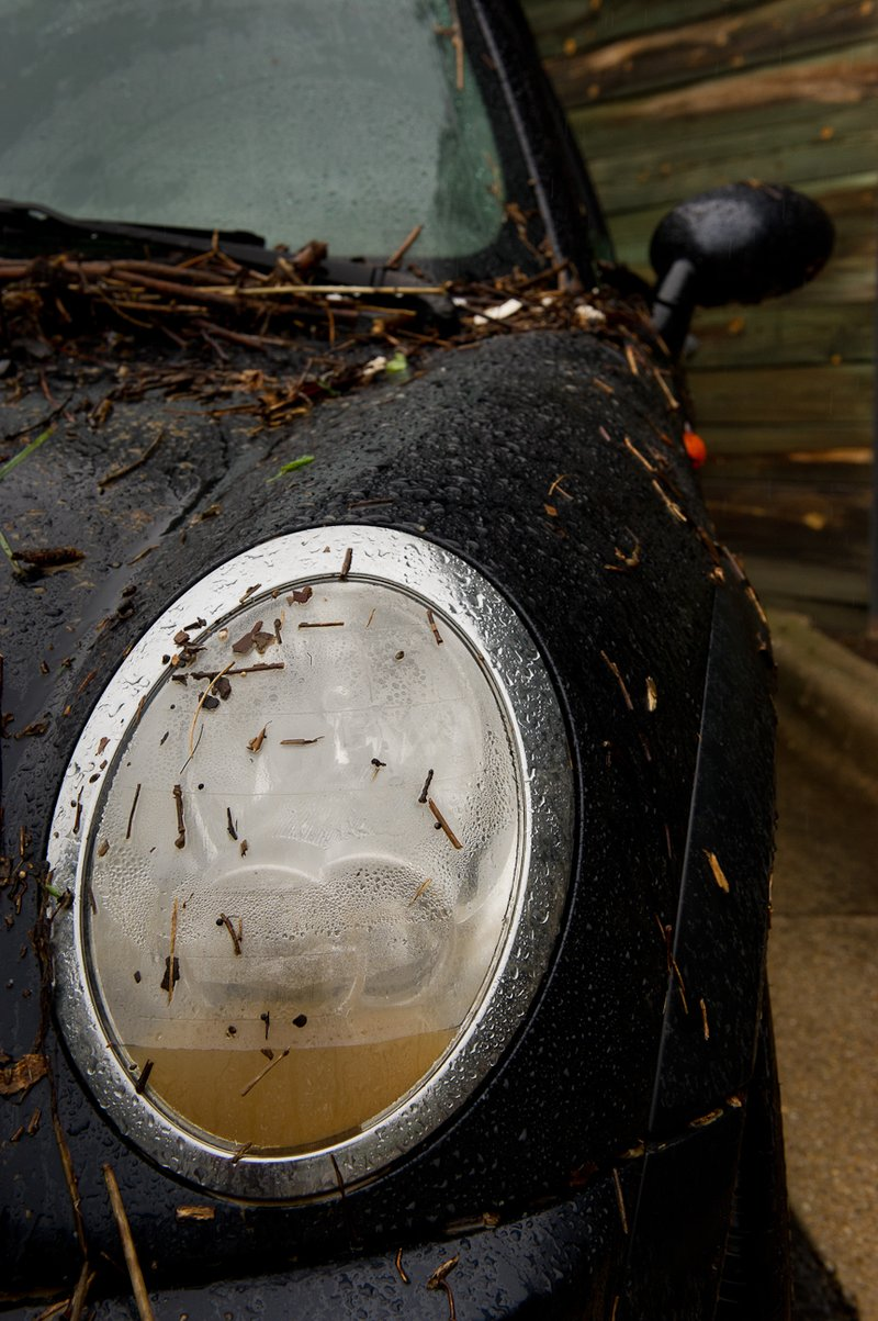 Muddy water sits inside the headlight of a Mini Cooper in the parking lot of a Courtyard Marriott hotel on Eisenhower Avenue in Alexandria, Va., on Sept. 9, 2011. The lot was flooded after heavy rains pounded the region the previous night. (Andr