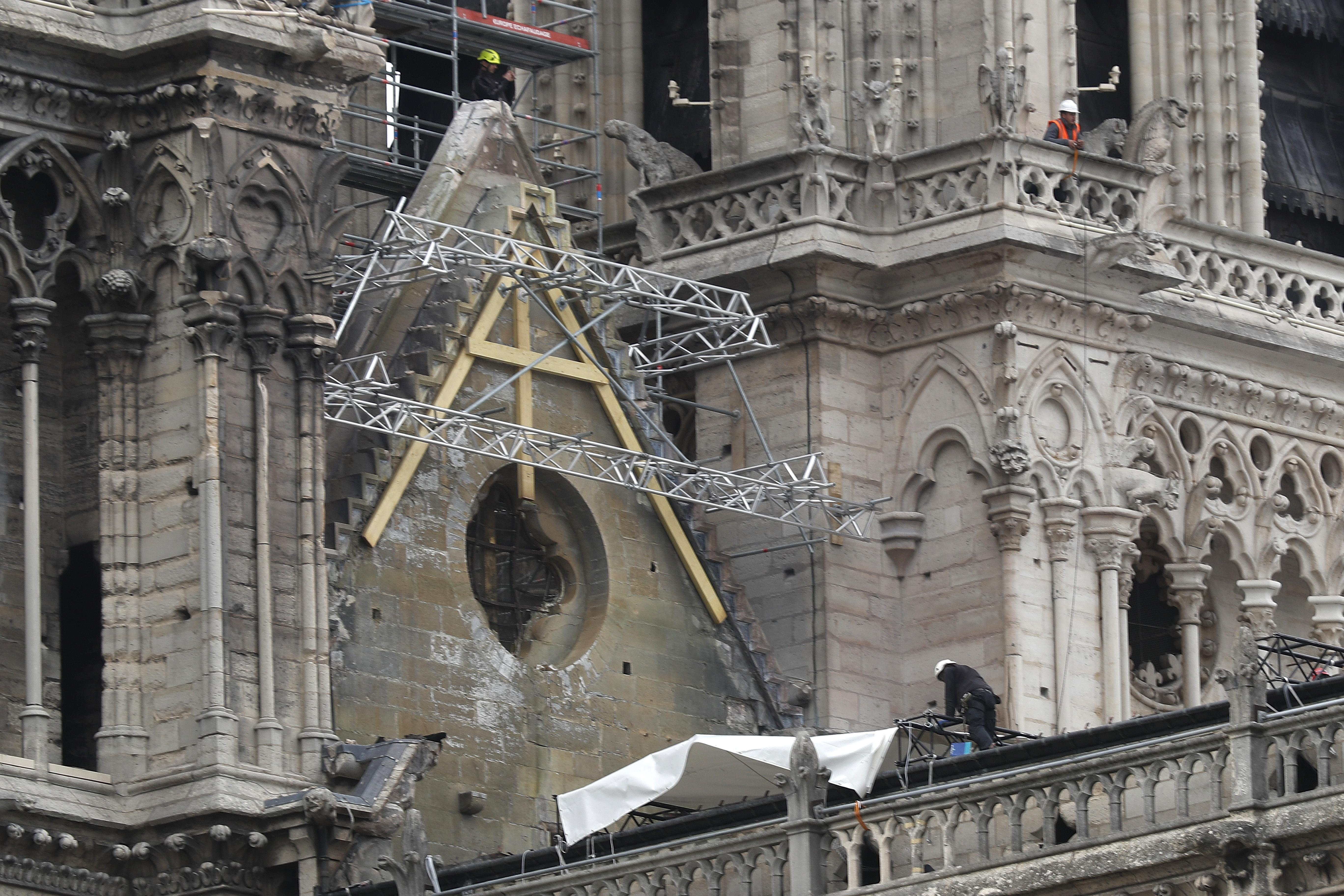 Mountain climbers install waterproof tarps to protect gutted Notre Dame